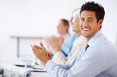 Buy stock photo Portrait of a smart young businessman with colleagues applauding at a seminar