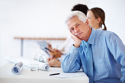 Buy stock photo Portrait of a bored businessman sitting in a corporate meeting with colleagues