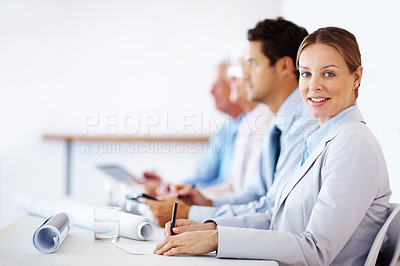 Buy stock photo Portrait of a smart young businesswoman writing notes while sitting in a pressentation