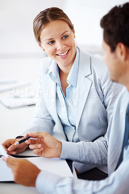 Buy stock photo Portrait of a beautiful young businesswoman sitting with her colleague discussing business plan