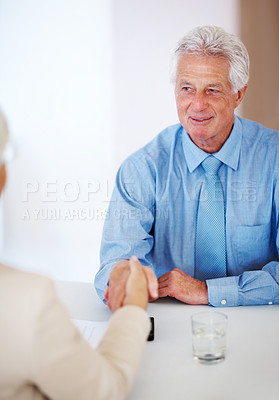 Buy stock photo Portrait of a confident old business man shaking hands with his colleague at office