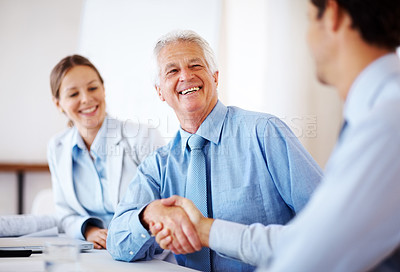 Buy stock photo Portrait of a two business men shaking hands with colleague at the back