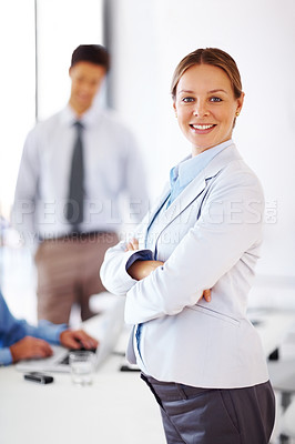 Buy stock photo Portrait of a smart young businesswoman standing with folded hand ahead of her colleagues