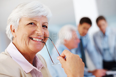 Buy stock photo Closeup portrait of a smiling old businesswoman holding glasses in mouth at office