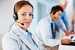 Confident call center executive with colleagues at back