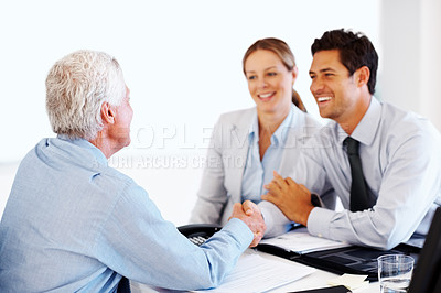 Buy stock photo Professional advisor shaking hand with a happy young couple at his workplace