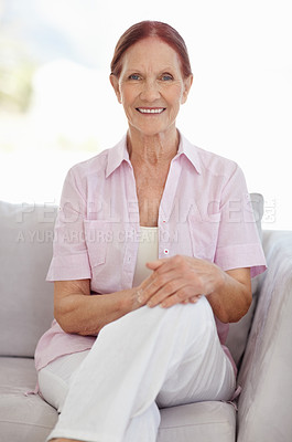 Buy stock photo Portrait of a happy matured woman sitting in sofa at home