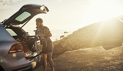Buy stock photo Cropped shot of a young woman taking her bicycle out from the trunk of of her car