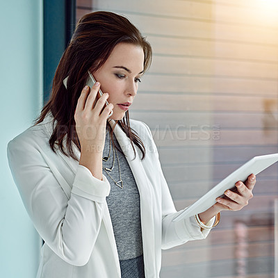 Buy stock photo Shot of a young businesswoman using a digital tablet and phone at work
