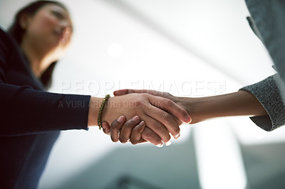 Buy stock photo Cropped shot of two creative businesspeople shaking hands