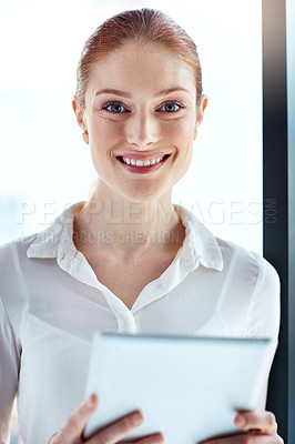 Buy stock photo Portrait of a happy young businesswoman using a digital tablet at work