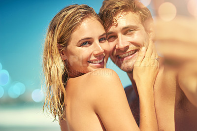 Buy stock photo Cropped shot of an affectionate young couple taking a selfie on the beach