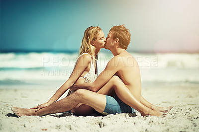 Buy stock photo Full length shot of an affectionate young couple sitting face to face on the beach
