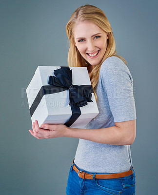 Buy stock photo Cropped studio shot of a happy young woman receiving a present
