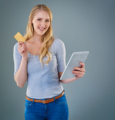 Buy stock photo Cropped studio shot of a young woman shopping online with tablet and her credit card