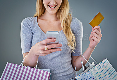 Buy stock photo Cropped studio shot of a young woman holding her smart phone, credit card and shopping bags