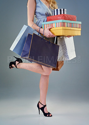 Buy stock photo Studio shot of a happy young woman holding a selection of shopping bags and gift boxes