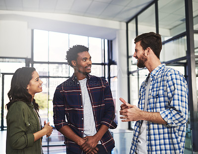 Buy stock photo Cropped shot of three young designers having a discussion in a modern office