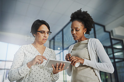 Buy stock photo Low angle shot of two businesswomen looking at a tablet in the office