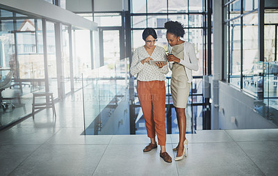 Buy stock photo Full length shot of two businesswomen looking at a tablet in the office
