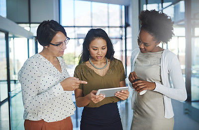 Buy stock photo Cropped shot of three businesswomen looking at a tablet in the office