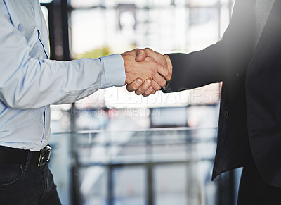 Buy stock photo Cropped shot of two unrecognizable businessmen shaking hands in an office