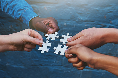 Buy stock photo Cropped shot of four people each holding a puzzle piece to fit together