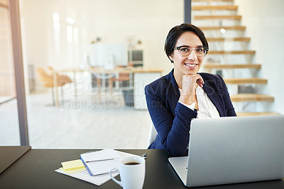Buy stock photo Portrait of a confident young businesswoman working on a laptop in a modern office