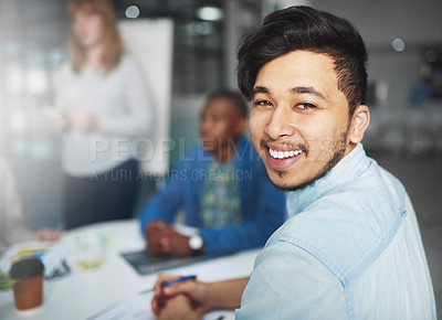 Buy stock photo Cropped portrait of a young businessman looking over his shoulder during a presentation in a boardroom