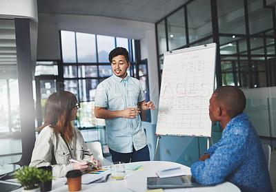 Buy stock photo Shot of a young businessman using a whiteboard to give a presentation to his colleagues in a boardroom