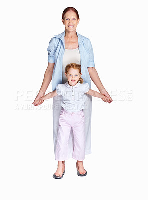 Buy stock photo Full length of a little girl standing on her grandmother feet isolated against white