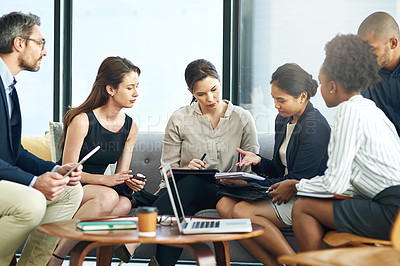 Buy stock photo Shot of a group of businesspeople discussing work during a boardroom meeting