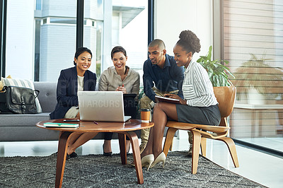 Buy stock photo Shot of a group of businesspeople working together over a laptop during a meeting