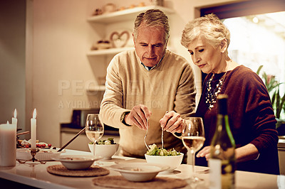 Buy stock photo Shot of an elderly couple dishing up a meal in their kitchen at home