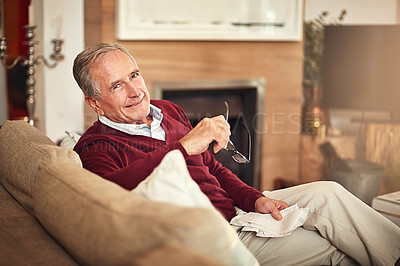Buy stock photo Portrait of a senior man sitting at home holding receipts