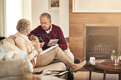 Buy stock photo Shot of a senior couple using a digital tablet at home