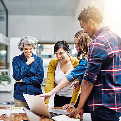 Buy stock photo Cropped shot of a group of creatives working together on a laptop in a modern office