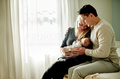 Buy stock photo Shot of a young married couple spending time with their newborn baby