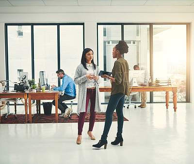 Buy stock photo Shot of young creatives having a discussion in a modern office
