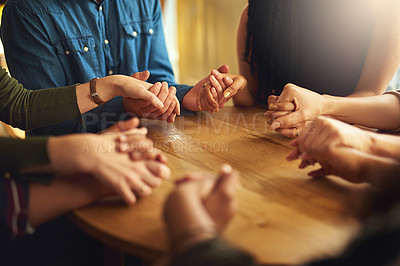 Buy stock photo Shot of a group of people holding hands and praying together