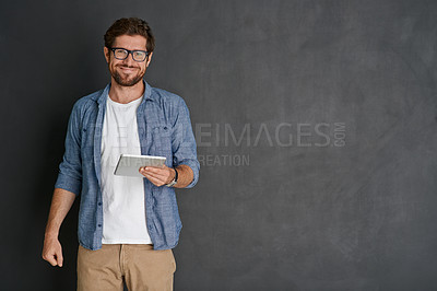 Buy stock photo Studio portrait of a young man using his tablet against a grey background
