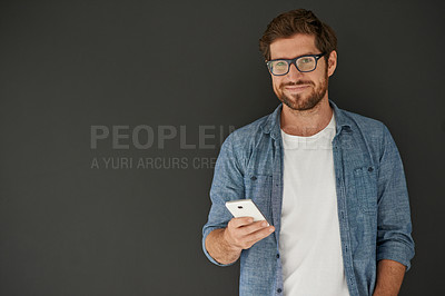 Buy stock photo Studio portrait of a young man reading a text message against a grey background