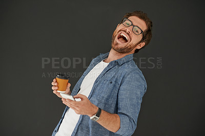 Buy stock photo Studio portrait of a young man laughing while drinking coffee and reading a text against a grey background