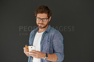 Buy stock photo Studio shot of a young man drinking coffee and sending a text against a grey background