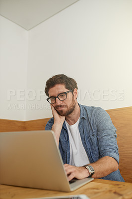 Buy stock photo Cropped shot of a young man looking bored while working on his laptop