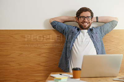 Buy stock photo Cropped portrait of a young man sitting with his hands behind his head working on his laptop