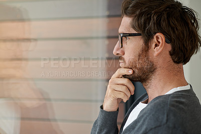 Buy stock photo Shot of a young entrepreneur looking thoughtfully out of his office window