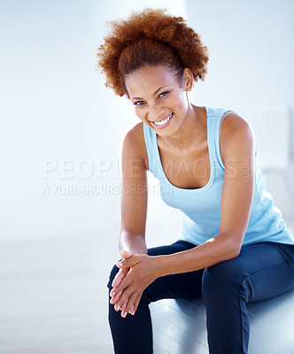 Buy stock photo Portrait of a cheerful young fit woman sitting on a exercise ball in the gym