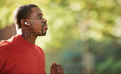 Buy stock photo Shot of a fit man using wireless earphones while out for run