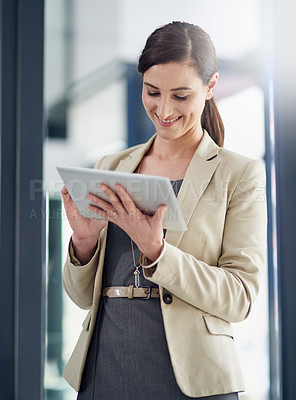 Buy stock photo Shot of a professional businesswoman using a digital tablet at work